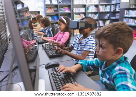 Side view of African-american schoolboy using virtual reality headset while his schoolmaes working o Stock photo © wavebreak_media