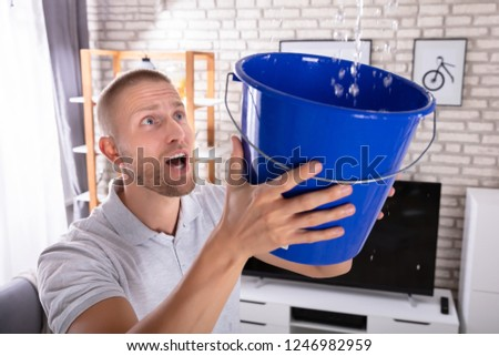 Man Holding Bucket While Water Droplets Leak From Ceiling Stock photo © AndreyPopov