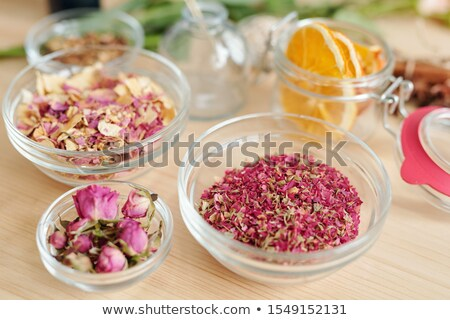 Three bowls with dry rose petals and rosebuds and small jar with orange slices Stock photo © pressmaster