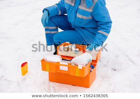 Young paramedic in workwear and gloves checking medicine and first aid items Stock photo © pressmaster