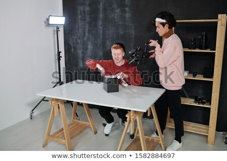 Young cameraman with video equipment shooting male vlogger opening box Stock photo © pressmaster
