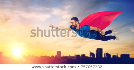 man in superhero cape flying over sunset in city Stock photo © dolgachov