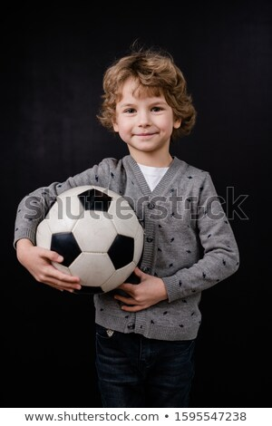 Happy little boy in casualwear holding soccer ball by chest in isolation Stock photo © pressmaster