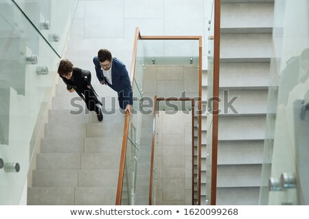 Overview of two young business people in formalwear walking upstairs Stock photo © pressmaster