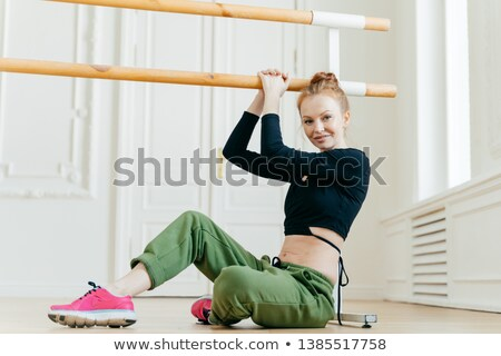 Female gymnast sits on floor, dressed in sport outware, stretches herself near barre, holds hand on  Stock photo © vkstudio