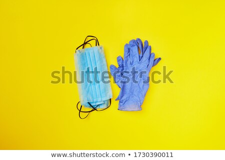 Two piles from medical masks and protective gloves on a yellow background. Stock photo © artjazz