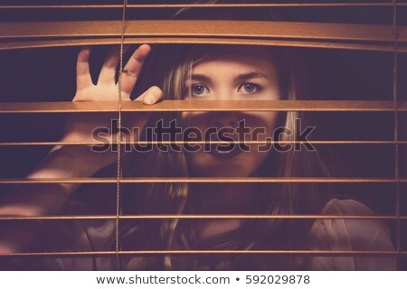 Closeup of a woman's eyes spying through blinds Stock photo © photography33