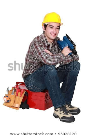 young tradesman sitting on toolbox holding sander machine Stock photo © photography33