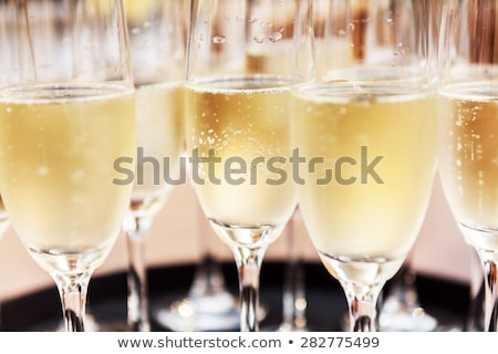 Stock fotó: Glasses Of Champagne With Bottles On White