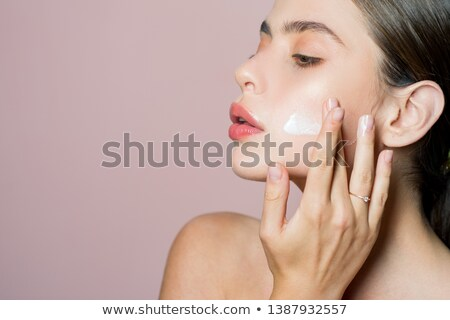a woman spreading out cosmetic cream on her face stock photo © photography33