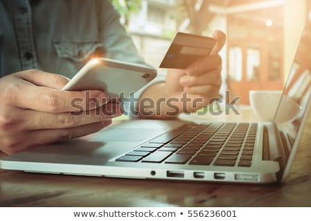 Mans hand holding debit card and using laptop Stock photo © stockyimages