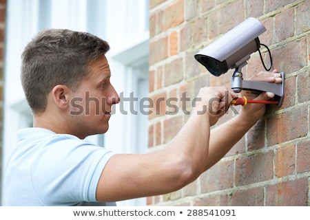 Security Consultant Fitting Security Camera To House Wall Stock photo © HighwayStarz