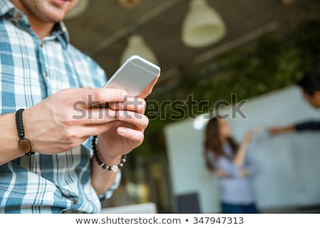 Hands of man using mobile phone while his partners arguing Stock photo © deandrobot
