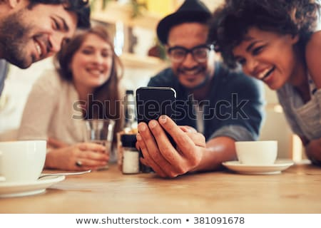 women having coffee and looking at pictures on smart phone stock photo © kzenon