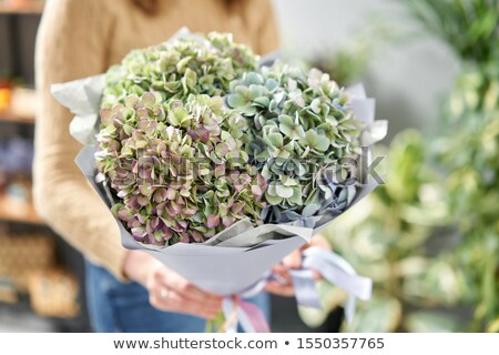 Stock photo: A green vase with fresh flowers