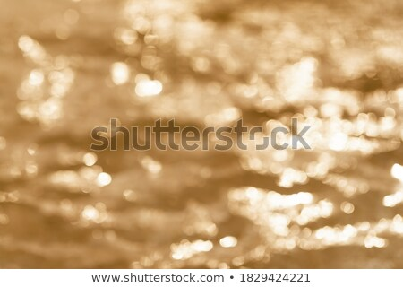 Defocused golden toned water surface texture background Stock photo © TasiPas