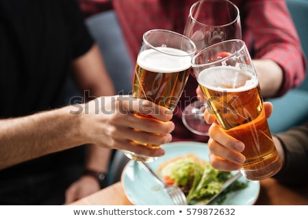 Happy friends sitting in cafe eating pizza while drinking alcohol stock photo © deandrobot