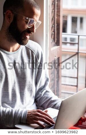 Sorridere barbuto giovane occhiali utilizzando il computer portatile giovani Foto d'archivio © deandrobot