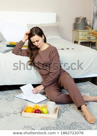 concentrated woman sitting indoors near cup of coffee stock photo © deandrobot