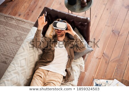 Happy man lies on sofa wearing virtual reality glasses. Stock photo © deandrobot