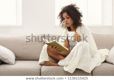 Young woman reading on couch Stock photo © IS2