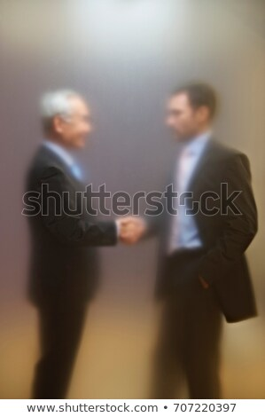 Men shaking hands behind frosted screen Stock photo © IS2