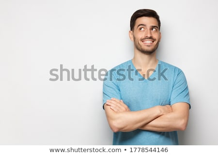 Handsome young man with arms crossed. Looking aside. Stock photo © deandrobot