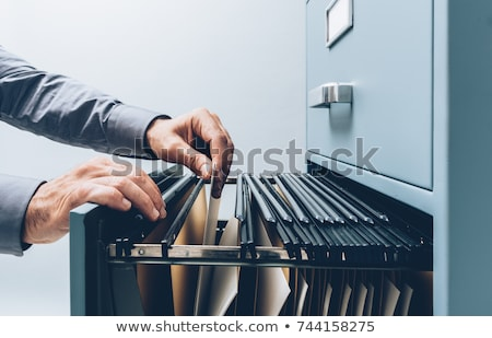Office clerk searching files in the filing cabinet Stock photo © stokkete