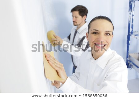 Woman grinding wall with sandpaper  Stock photo © dash