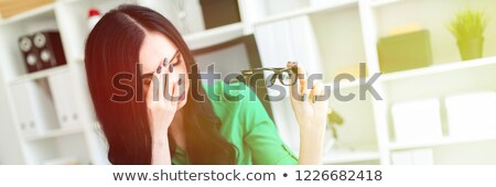 Stock photo: A young girl is sitting in the office at the table rubbing her face and holding glasses in her hand.