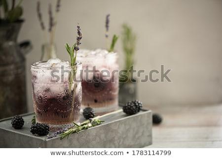 Lavender lemonade with lemon and ice on black background. Stock photo © Illia