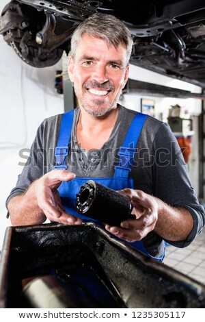 Foto d'archivio: Smiling Mature Man Holding The Oil Filter Of A Car