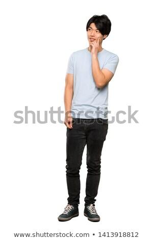 Portrait a pensive young man standing Stock photo © deandrobot