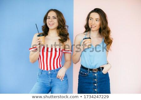 Image of two beautiful women wearing hats holding takeaway coffe Stock photo © deandrobot