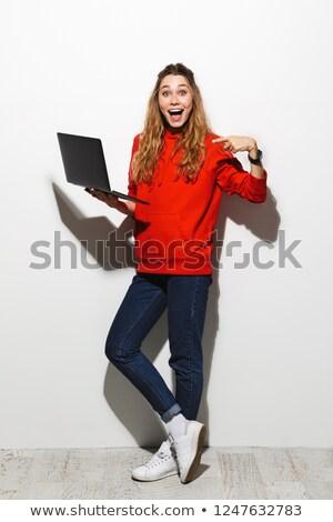 full length photo of optimistic woman 20s wearing red sweatshirt stock photo © deandrobot