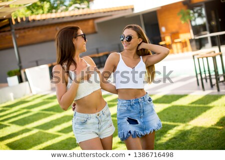 Two pretty young women posing in courtyard at hot summer day Stock photo © boggy