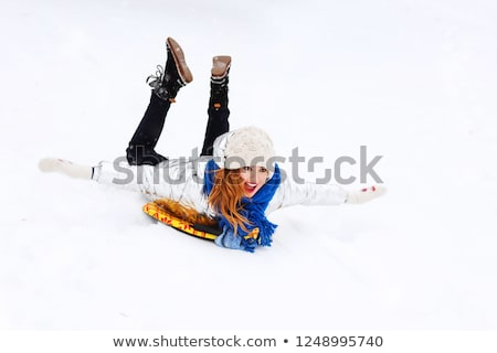 girl sliding down on snow saucer sled in winter Stock photo © dolgachov