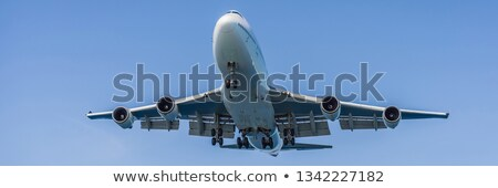 a white airplane flying in a clear pale blue sky banner long format stock photo © galitskaya