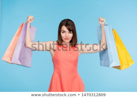 Young brunette female shopper lifting paperbags after successful shopping Stock photo © pressmaster