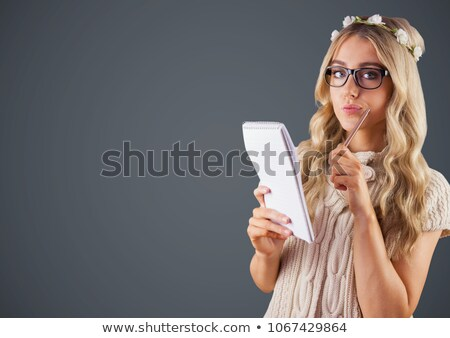 Millennial woman with flowers in hair and notepad against grey background Stock photo © wavebreak_media