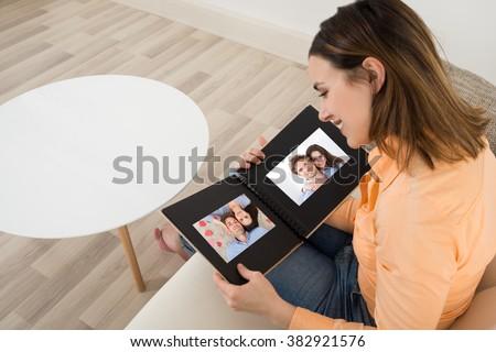 Woman Looking At Photo Album Stock photo © AndreyPopov