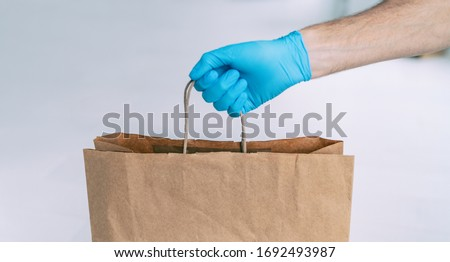 Grocery store shopping delivery man giving paper bag wearing blue glove as protection for COVID-19 C Stock photo © Maridav