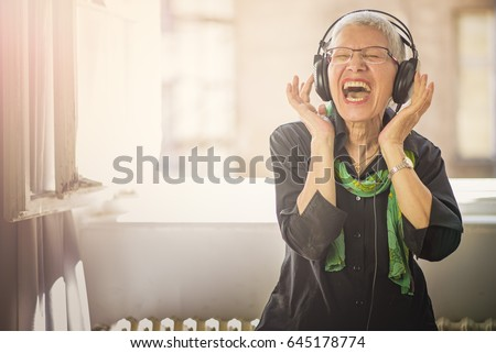 senior woman in headphones listening to music stock photo © dolgachov