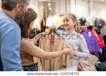 Pretty girl showing her parents beige cashmere pullover with discount Stock photo © pressmaster