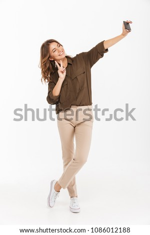 Photo of cute young woman taking selfie photo on smartphone Stock photo © deandrobot