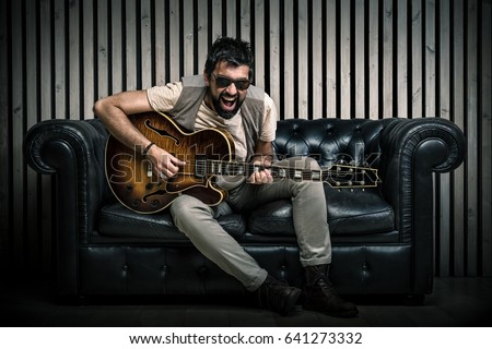 beautiful guitarist sitting on couch stock photo © sumners