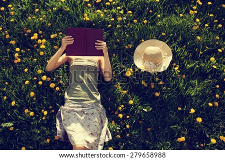 Girl lying in meadow reading stock photo © lichtmeister