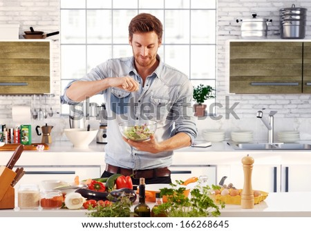 Handsome young man preparing food at home Stock photo © boggy