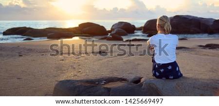 Feminino sessão areia assistindo nascer do sol praia Foto stock © lovleah