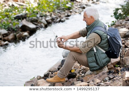 Aged man in activewear pointing at touchpad display while sitting on river bank Stock photo © pressmaster
